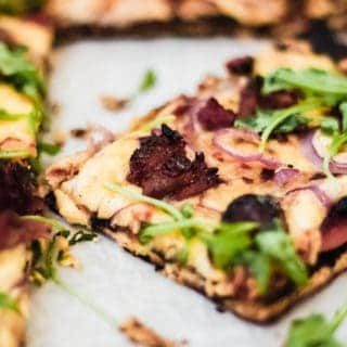 grilled bbq pizza on parchment paper with bbq ribs and red onion